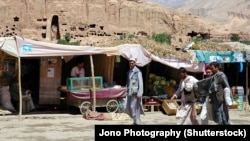 Market stalls in Bamiyan stand in front of one of the niches where the region's famed carved Buddhas, which were blown up by the Taliban in 2001, once stood.
