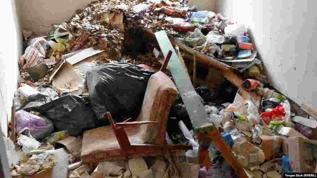 Свалка мусора и домашних вещей в одной из комнат первого этажа