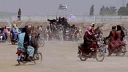 PAKISTAN -- Supporters of the Taliban carry the Taliban's signature white flags in the Afghan-Pakistan border town of Chaman, Pakistan, Wednesday, July 14, 2021.