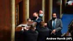 Полиция Капитолия США с оружием в руках стоит возле баррикадной двери, когда протестующие пытаются проникнуть в палату Конгресса США в Капитолии в среду, 6 января 2021 года, в Вашингтоне.