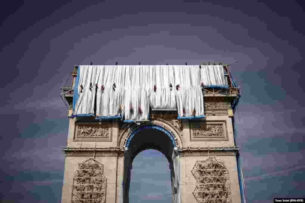 """Alpiniști utilitari lucrează la asamblarea instalației de artă """"Arcul de Triumf Înfășurat"""", realizată de regretatul artist Christo, la Paris, Franța, 12 septembrie 2021. Instalația monumentală a înfășurat monumentul parizian cu 25.000 de metri pătrați de țesătură argintie și albastră, în perioada 18 septembrie - 03 octombrie 2021. Artistul american Christo s-a născut în Bulgaria și a încetat din viață în mai 2020, iar Jean-Claude a murit în 2009."""