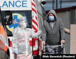 Медицинский работник помогает пациенту, пока другие машины скорой помощи с пациентами ждут возле больницы людей, инфицированных коронавирусной болезнью в Киеве, 30 марта 2021 года
