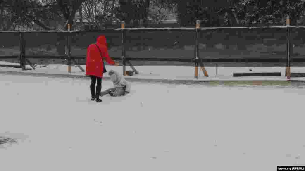 Малыши радуются выпавшему снегу: возможность поваляться в сугробах в Керчи выпадает нечасто. Родители спешат вывести детей на прогулку, чтобы насладиться снежной погодой: местные жители знают, что на Керченском полуострове погода переменчива
