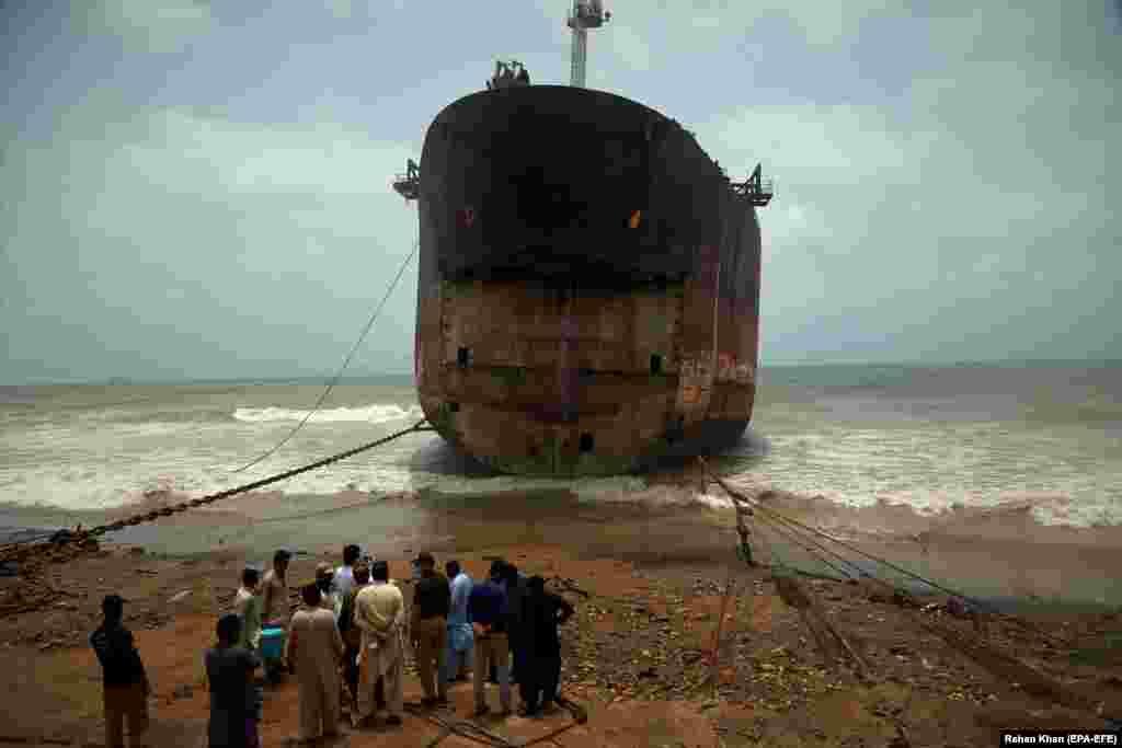 Люди стоят рядом с судном, содержащим тонны опасных химикатов в пакистанском порту Гадани 28 мая