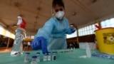 Коронавирус вакцинасының дозасын үстелге қойып жатқан медицина қызметкері. Көрнекі сурет.