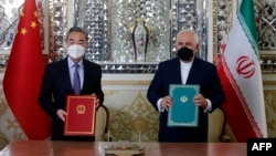 Iranian Foreign Minister Mohammad Javad Zarif (right) and his Chinese counterpart, Wang Yi, after signing a cooperation agreement in the capital, Tehran, on March 27