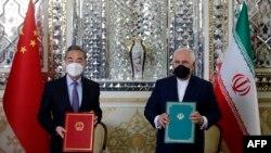 Ministri i Jashtëm i Kinës, Wang Yi, dhe ministri i Jashtëm i Iranit, Mohammad Javad Zarif, duke nënshkruar një marrëveshje në Teheran, më 27 mars, 2021.