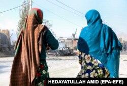 Două femei afgane stau lângă locul unei explozii din Kabul, Afganistan, 27 octombrie 2020. Cel puțin trei persoane au fost ucise și alte doisprezece rănite în explozia unei mașini capcană.